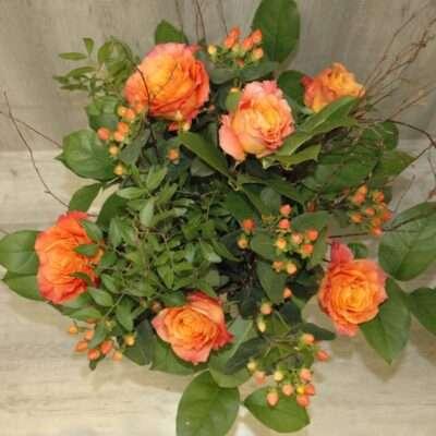Ramo de rosas naranjas, madera e hipericum